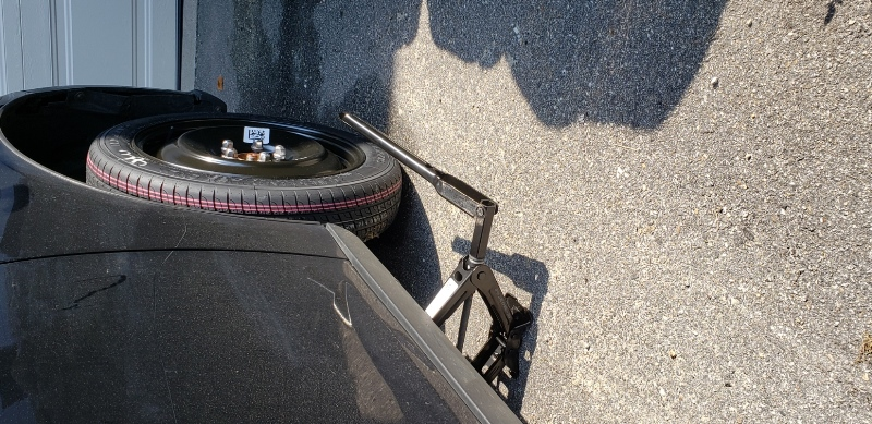 Car tire with donut and jack stand