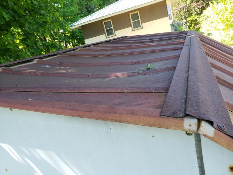 Roof dip of metal shed-tree side